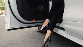 Women`s heels come out of an expensive car. Woman legs in high heels at the car in the city, urban stock footage