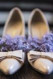 Women& x27; s high-heeled schoenen en lilac bloemen binnen voor het op smaak brengen van de binnenzool Stock Foto's