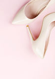 Women's high-heeled shoes. Pair of beige women's high-heeled shoes on pink background Royalty Free Stock Images