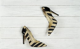 Women`s high-heeled shoes. On a white wooden background Royalty Free Stock Photo