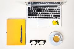 Women`s home office desk. Workspace with laptop, computer, yellow notebook, fashion glasses, cup of coffee and flower isolated on royalty free stock photos