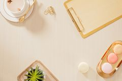 Women`s home office workspace with clipboard, macaroons, pen, coffee mug on pastel background. Flat lay, top view lifestyle. Concept royalty free stock photography