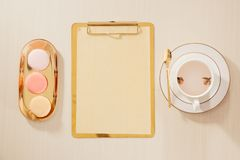 Women`s home office workspace with clipboard, macaroon, coffee mug on pastel background. Flat lay, top view lifestyle concept stock image
