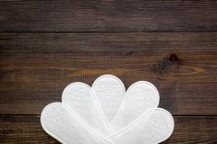Women`s hygiene products. Critical days concept. Sanitary pads on dark wooden background top view copy space. Women`s hygiene products. Critical days concept royalty free stock image