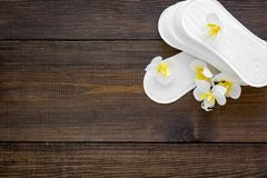 Women`s hygiene products. Critical days concept. Sanitary pads near small flowers on dark wooden background top view.  royalty free stock photography