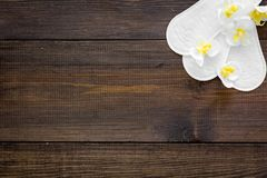Women`s hygiene products. Critical days concept. Sanitary pads near small flowers on dark wooden background top view.  stock images