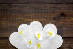 Women`s hygiene products. Critical days concept. Sanitary pads near small flowers on dark wooden background top view.  royalty free stock photo