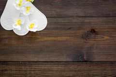Women`s hygiene products. Critical days concept. Sanitary pads near small flowers on dark wooden background top view.  royalty free stock images