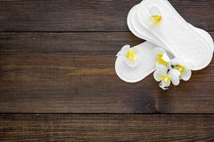 Women`s hygiene products. Critical days concept. Sanitary pads near small flowers on dark wooden background top view.  stock photography