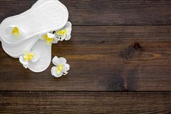 Women`s hygiene products. Critical days concept. Sanitary pads near small flowers on dark wooden background top view.  stock photo