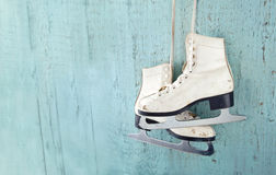 Women's ice skates hanging on blue wooden background Royalty Free Stock Photography