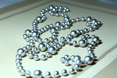 Women`s jewelry beads of steel color lie on a table on a beige n. Apkin with diagonal lines Royalty Free Stock Photo