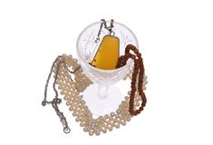Women's jewelry and glass. Women's jewelry - beads, framed amber, pearls and glass on a white background Stock Photos