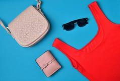 """Women& x27; s kleding en toebehoren die op een blauwe achtergrond wordt opgemaakt Rode T-shirt, beurs, zak, sunglassesï"""" Hoogste  stock afbeelding"""
