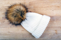 Women`s knitted white hat with fur pompon Royalty Free Stock Photography