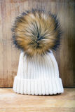 Women`s knitted white hat with fur pompon Stock Image