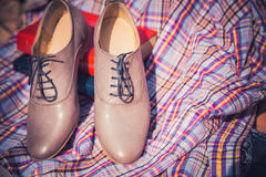 Women's leather shoes with laces are on a checkered tablecloth Stock Images