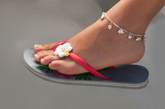 Women's leg with a bracelet in thong Royalty Free Stock Image