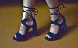 Women`s legs in beautiful black sandals with high heels and lacing. Women`s shoes stock image