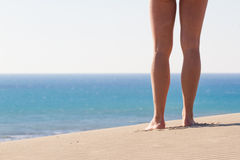 Women's legs from behind. Recreation. Blue sea. Women's legs from behind. Recreation. Footprints. Sand texture Royalty Free Stock Photos