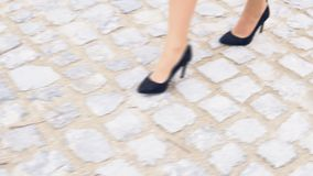 Women`s legs in black shoes on a stone road. 1 stock video