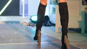 Women`s legs in black suede boots on high shiny heel go along podium on fashion show