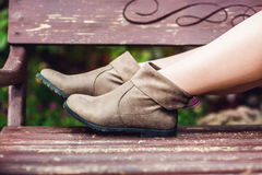 Women`s legs in leather boots. Woman resting in the park.  Royalty Free Stock Images