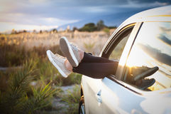 Women's legs out of car window Stock Images