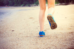 Women's legs running or walking along the beach. Stock Photo