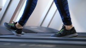 Women`s legs are slowly walking on the treadmill. 4K Slow Mo stock footage