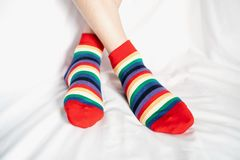 Women`s legs in socks colors alternating, side stand on white fabric floor. Women`s legs in socks colors alternating, side stand on white fabric floor royalty free stock photos