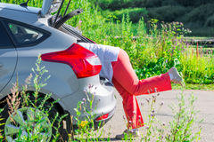 Women's legs sticking out of the trunk of the car Stock Photography