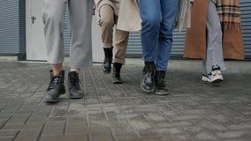 Women walk near wall. Women`s legs tread on the background of a striped wall. Students walk near the wall stock video footage