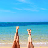 Women's legs up with tropical beach background. Royalty Free Stock Images