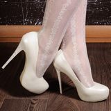 Women's legs in white high-heeled shoes with rhinestones. stock photography