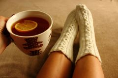 Women`s legs in white knitted socks with winter pattern on beige veil with cup of black tea and lemon slice in hand top view. Stock Photos