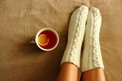 Women`s legs in white knitted socks with winter pattern on beige veil with cup of black tea and lemon slice top view. Stock Images