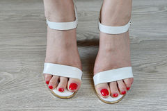 Women's legs and white sandals Royalty Free Stock Photography