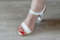 Women's legs and white sandals Stock Photography
