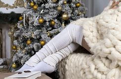 Women`s legs in white socks, white knitted blanket, a Christmas. Tree decorated with pine cones and gold balls, a book ,a piece of chocolate, the eve of the Royalty Free Stock Images