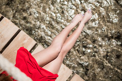 Women`s legs at wooden pier over sea water on summer resort. Summer vocation. Royalty Free Stock Images