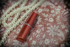 Women`s lipstick, a necklace on fabric with Oriental ornaments. Vintage stock photo