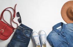 Women& x27; s manierkleding en toebehoren Jeans, denimoverhemd, tennisschoenen, vilten hoed, leerzak, zonnebril, lay-out stock afbeelding