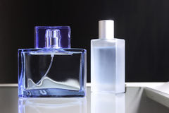 Women`s and men` fragrance. Male and female perfume in a glass bottle stock image