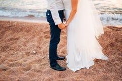 Women`s and men`s feet in the sand. Wedding in Montenegro Stock Photos