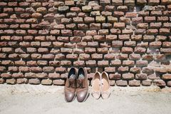 Women's and men's shoes are near the wall stock images