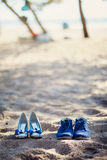 Women`s and men`s shoes on the sand. Two pairs of shoes in the sand Royalty Free Stock Images