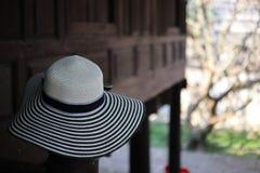 Women& x27; s-Modehüte auf thailändischen Holzhäusern, Pastellhintergrund stockfoto