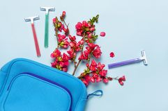 Women`s multi-colored disposable razors, cosmetic bag, pink flowers on a pastel blue background, top view Flat lay copy space. royalty free stock image