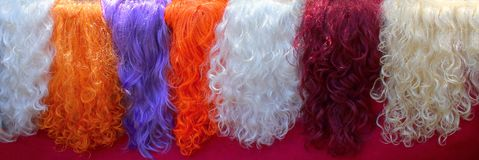 Women`s multi-colored wigs, white, orange, red, blue Stock Images